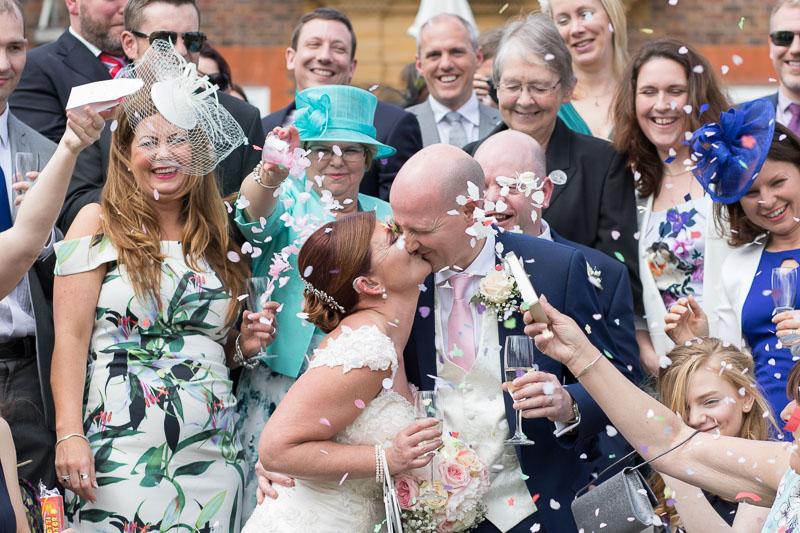 Surrey wedding photographer - Bride and groom kissing for confetti shot at Barnett Hill Hotel