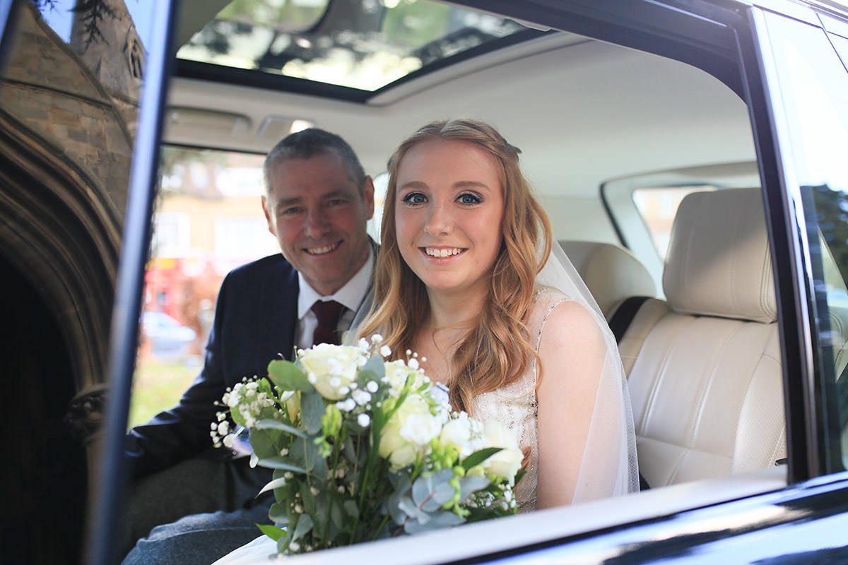 bride and her father arrive at St Michael's church in Camberley, in the car with the church reflected on the side of the car taken by Surrey wedding photographer