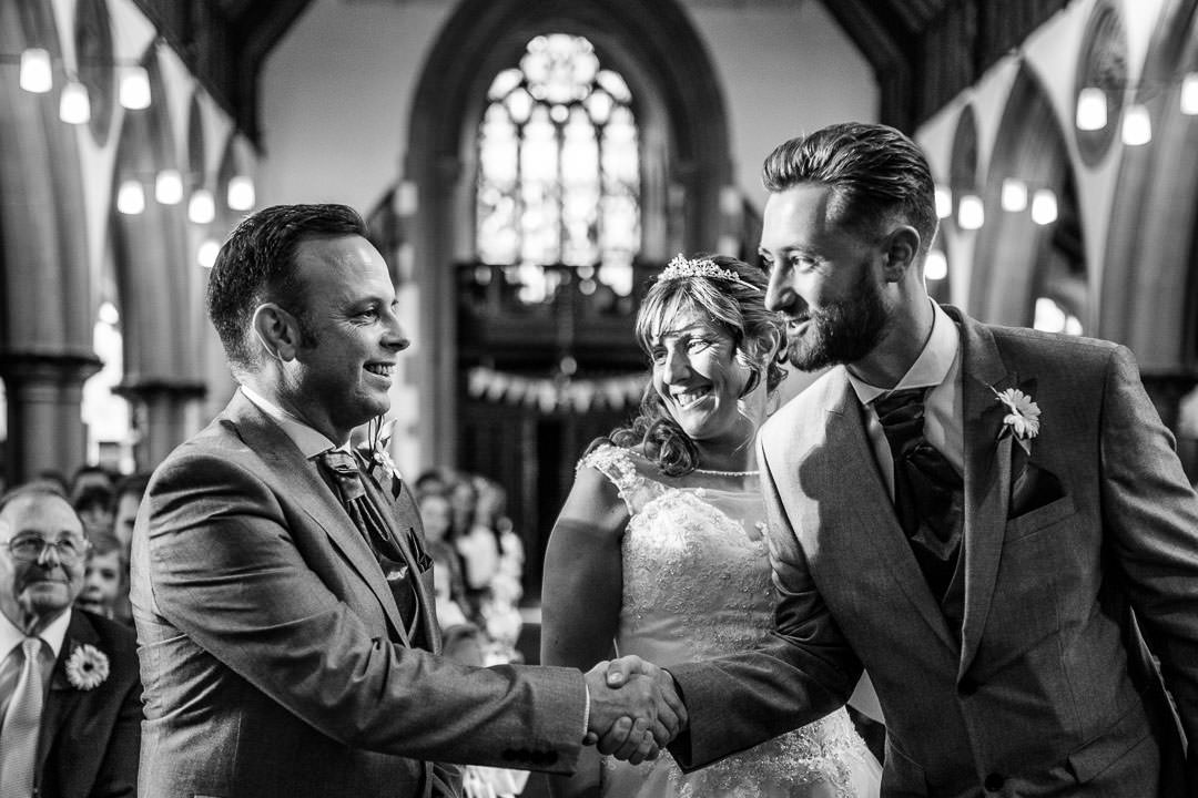 black and white photograph of the groom shaking hands with the bride's son at st Michael's church in Camberley, surrey
