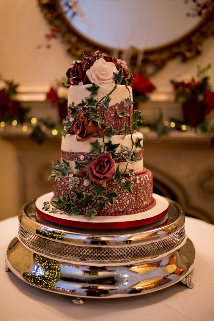 three tiered white wedding cake decorated with red lace icing and roses and ivy at The Elvetham near Hartley Wintney in Hampshire