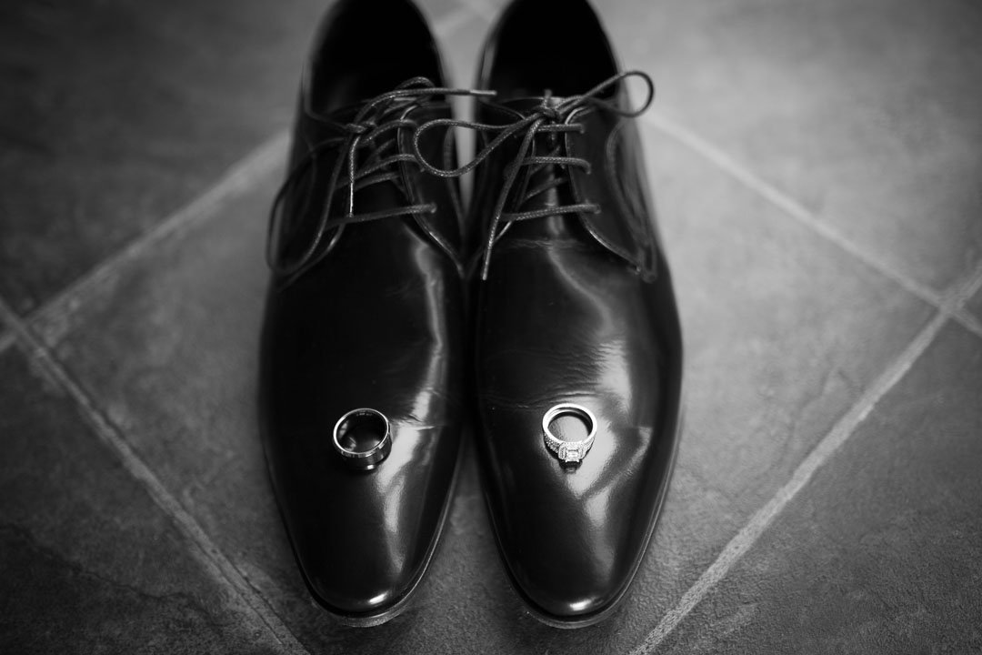 black and white photo of groom's shoes and rings at the Village Hotel in farnborough