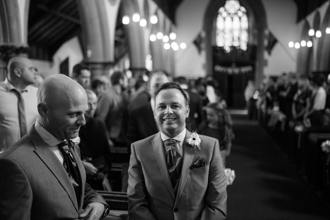 smiling groom waits for the bride to arrive at St Michael's church in Camberley