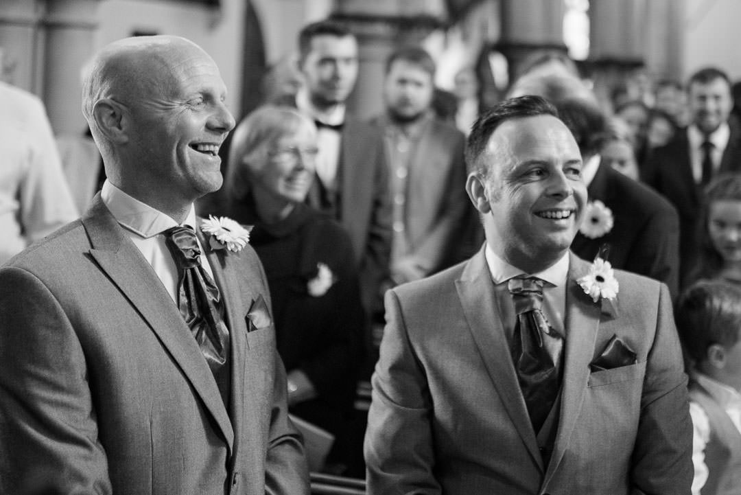 Groom and best man laughing at St Michael's church in Camberley