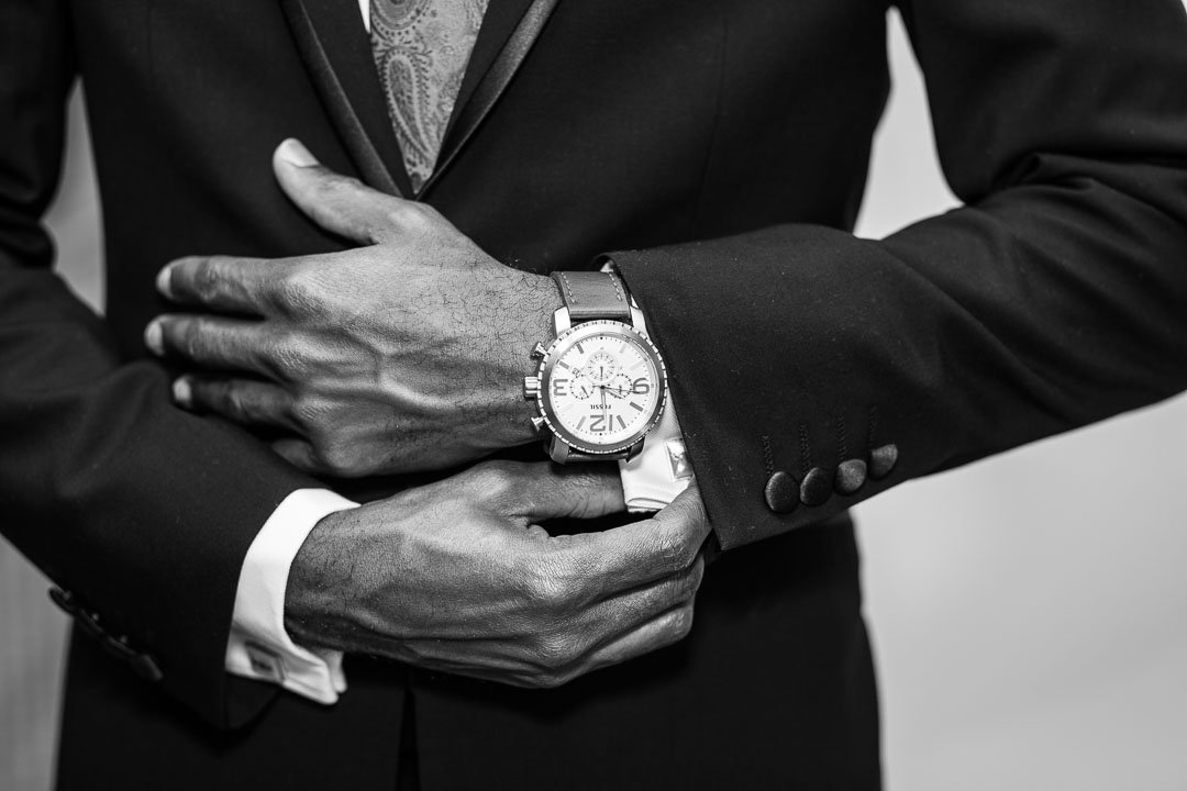 black and white photo of groom adjusting cufflink and fossil watch at the Village Hotel in farnborough