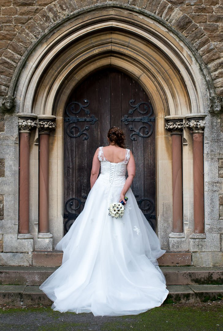bride stands on church steps to show full length of the back of her at st Michael's church in Camberley, surrey