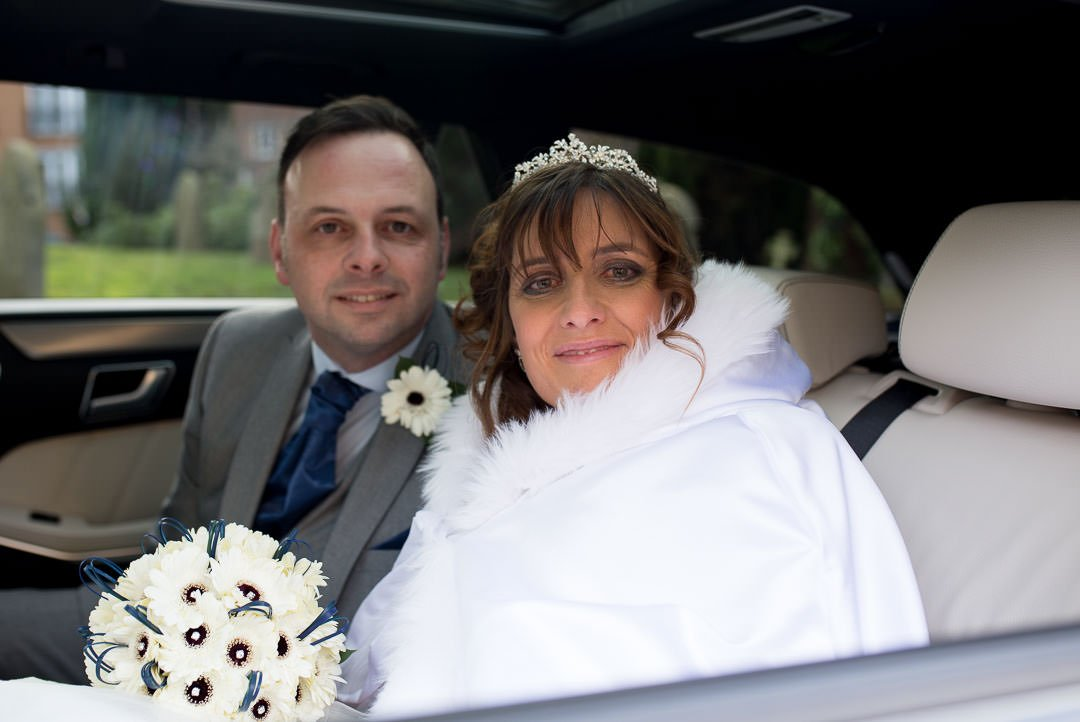Bride in full length fur lined cloak with her groom in the wedding car at st Michael's church in Camberley, surrey