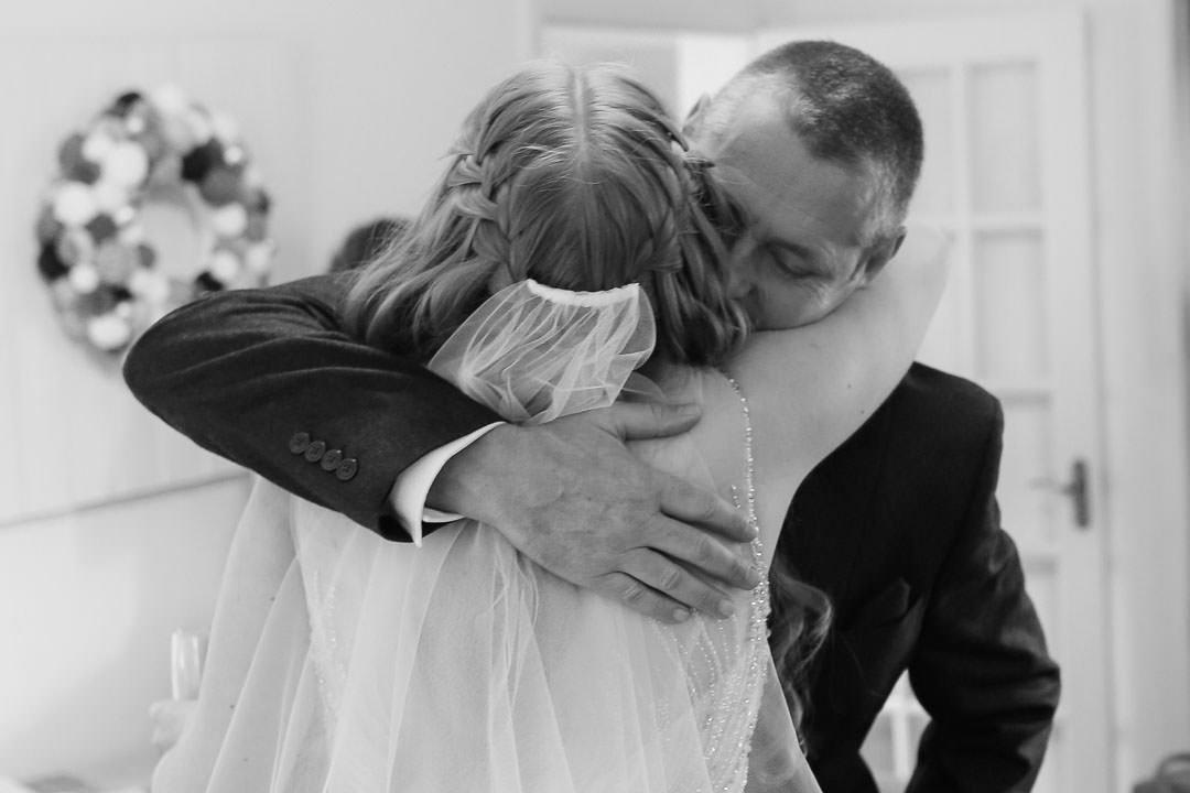proud dad hugs his daughter the bride