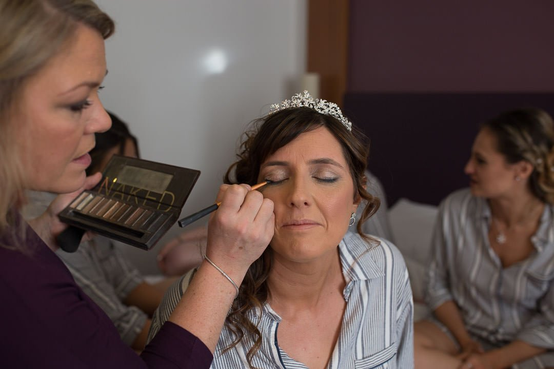 Bride having her make up done, wearing a tiara