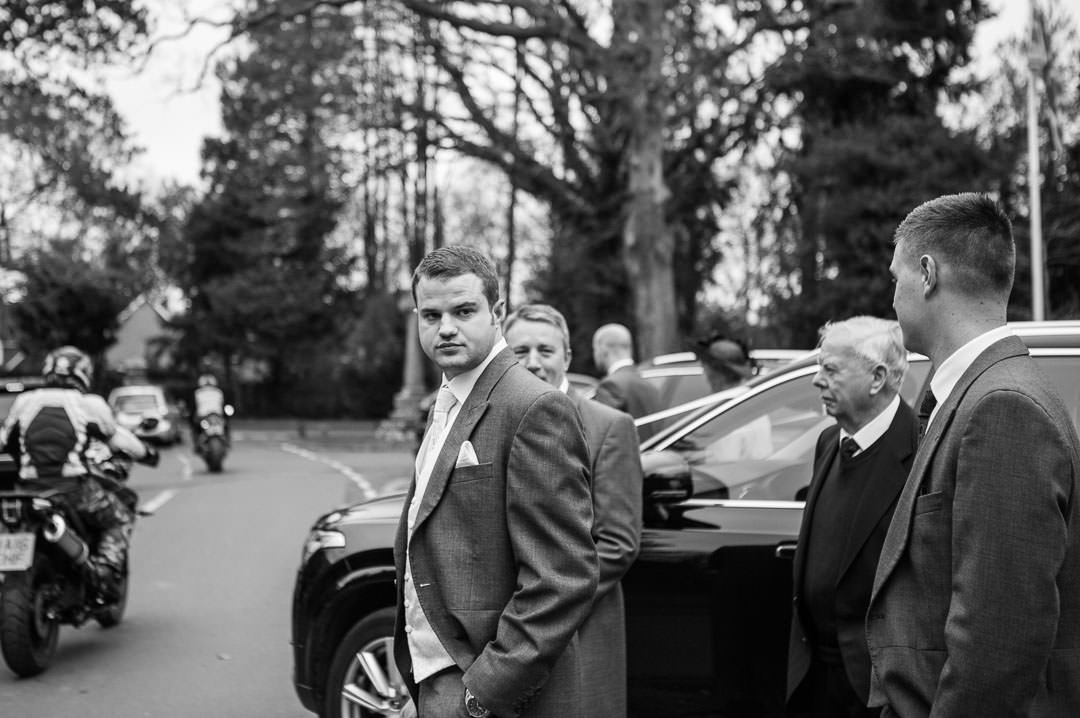 Black and white photo of the groom arriving at St Leonards church in Berkshire, surrounded by relatives