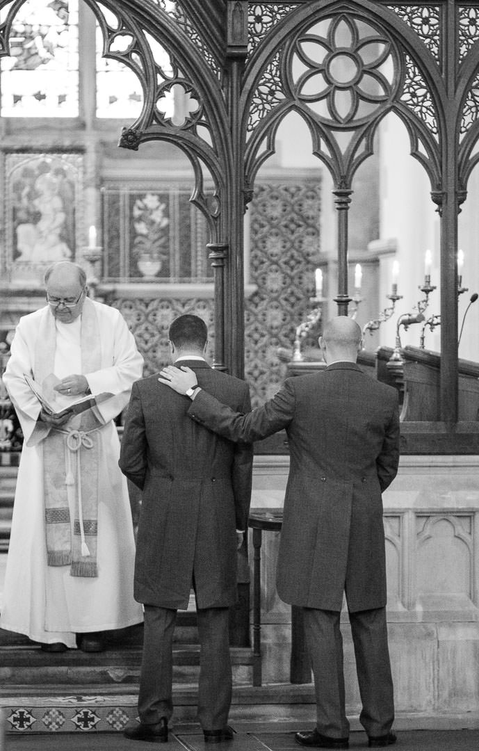 Bestman puts his hand on the groom's shoulder as they wait for the bride at the front of the church at Woodcote in Berkshire