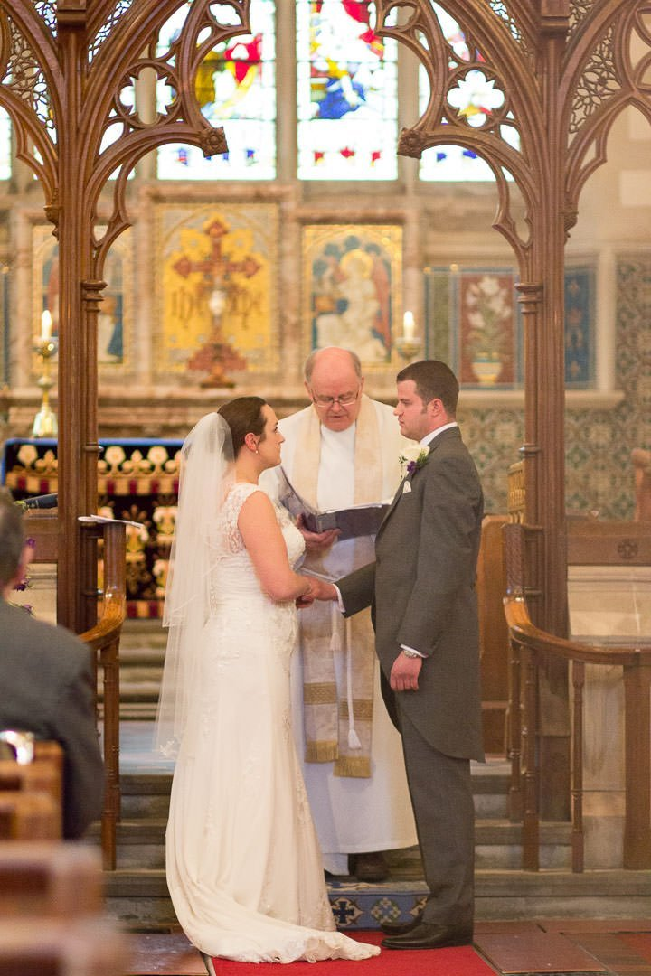 Bride and groom say their vows to each other in the church in front of the vicar at St Leonards church at Woodcote in Berkshire
