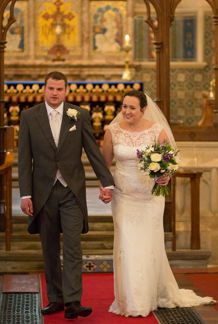 Bride and groom just married walk back down the aisle at St Leonards chucrh at Woodcote in Berkshire