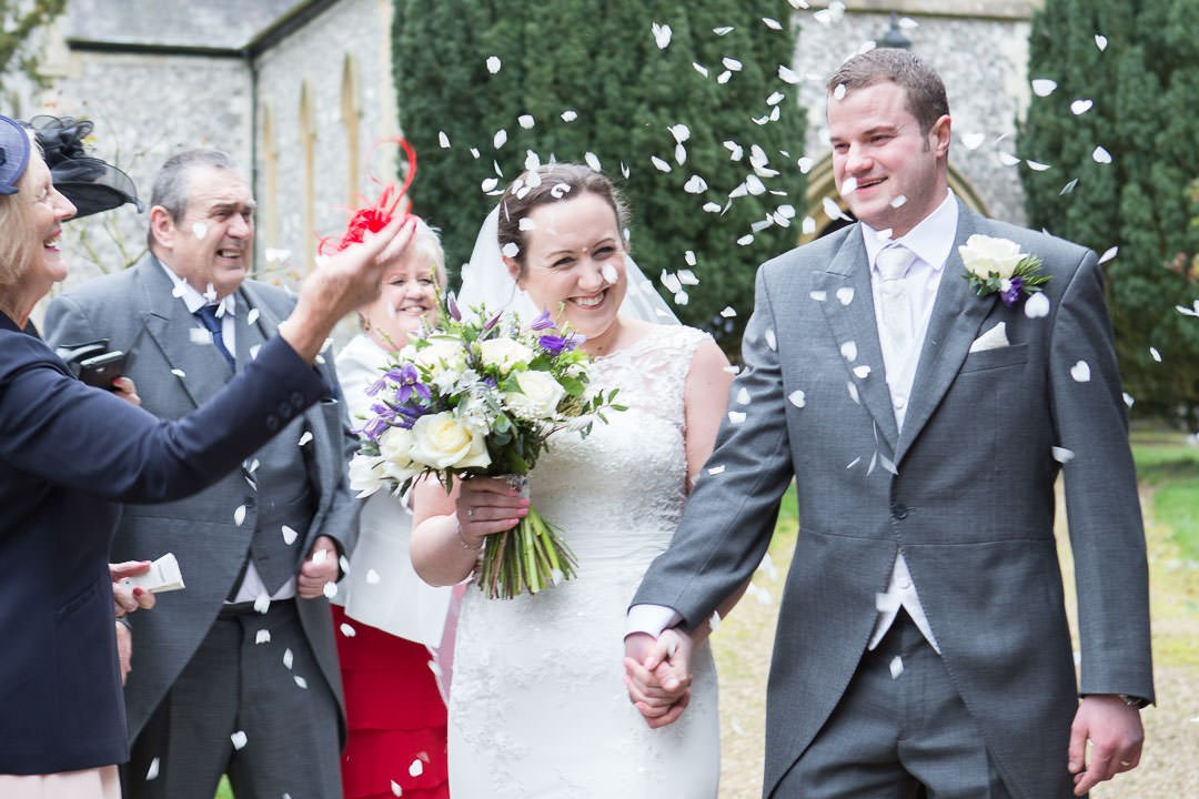bride and groom laughing as they walk hand in hand and people throw confetti at St Leonards Church at Woodcote in Berkshire