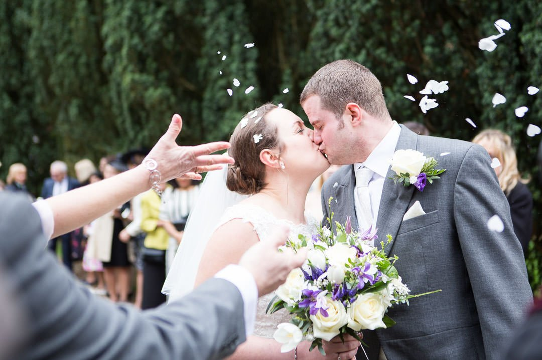 Bride and groom kissing as people throw confetti at St Leonards at Woodcote in Berkshire