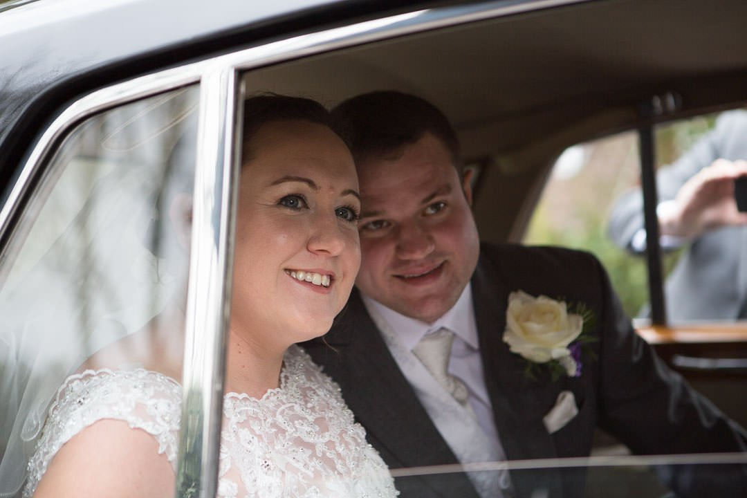 Bride and groom look out of car window outside St leonards church at Woodcote in Berkshire