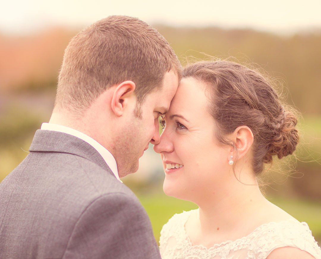 Bride and groom look at each other with foreheads touching at Sandford Springs