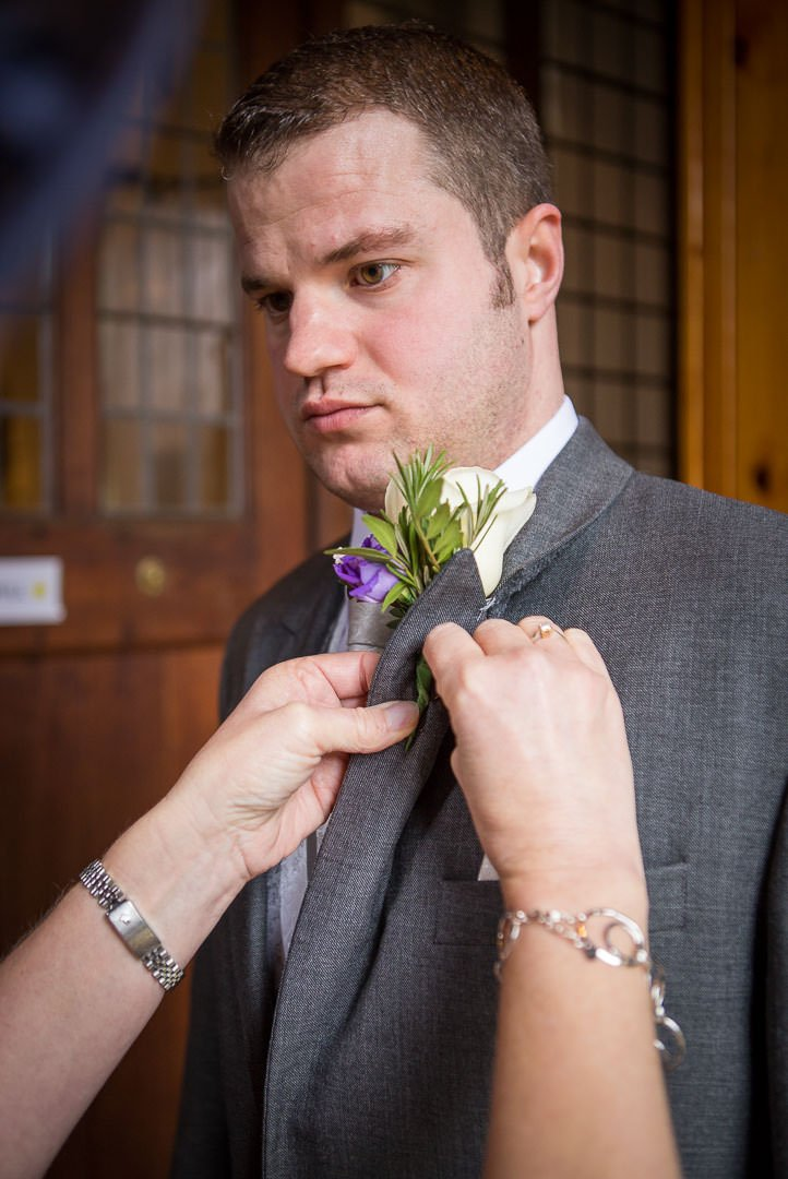Mother of the groom pins the groom's buttonhole onto his lapel at St Lenards church At Woodcote in Berkshire