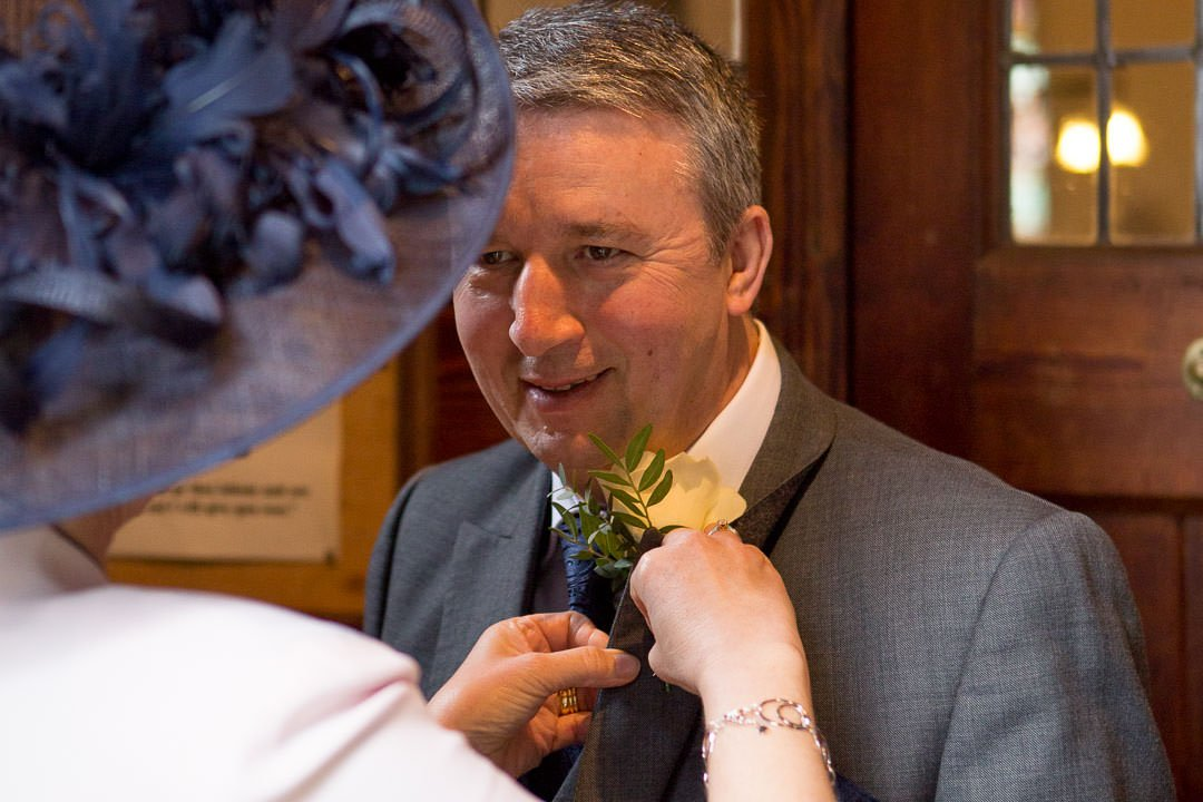 Mother of the groom helps father of the bride with the buttonhole at St Leonards church at Woodcote in Berkshire