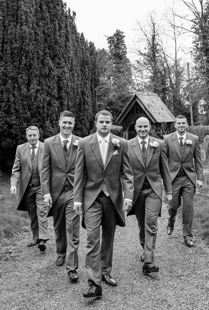 Black and white photo of the groom and groomsmen walk up the church pathof St Leonards in Woodcote, reservoir dogs style