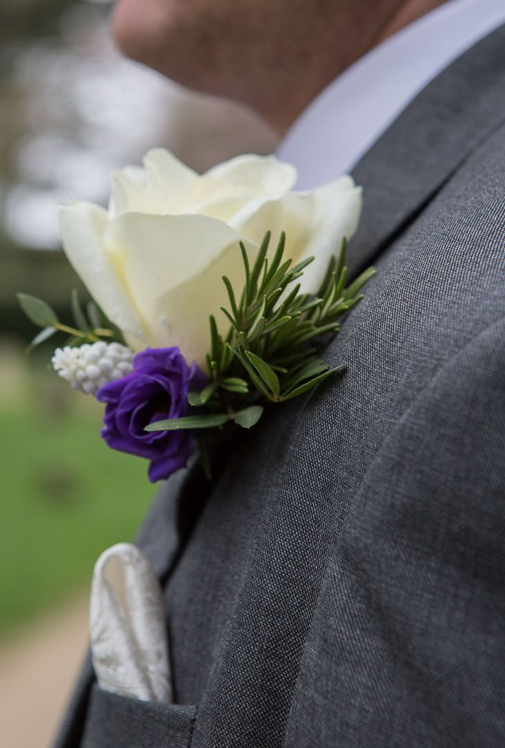 groom's buttonhole with white rose, white muscari, rosemary and purple lisianthus