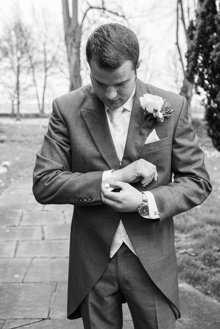 black and white photo of the groom adjusting his cufflinks outside St Leonards church in woodcote, Berkshire