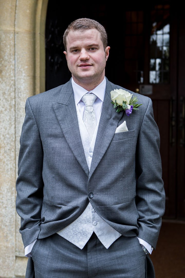 groom wearing grey morning suit standing in front of St Leonards church at Woodcote in Berkshire