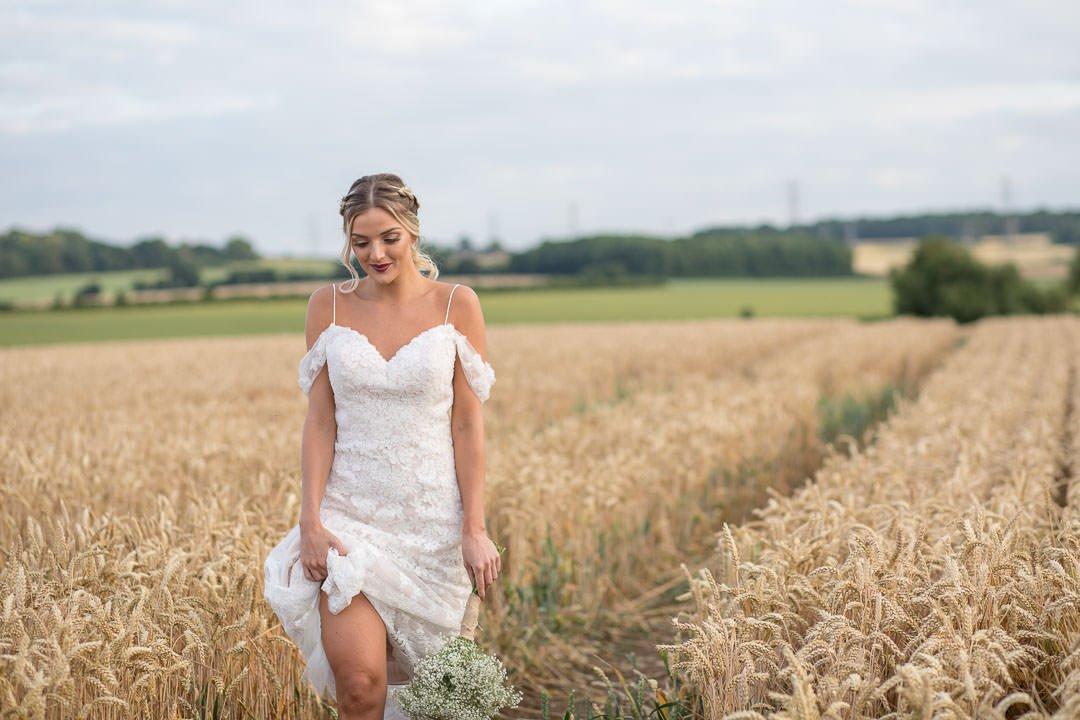 boho bride wearing white lace dress hitched up as she walks across a Hampshire cornfield