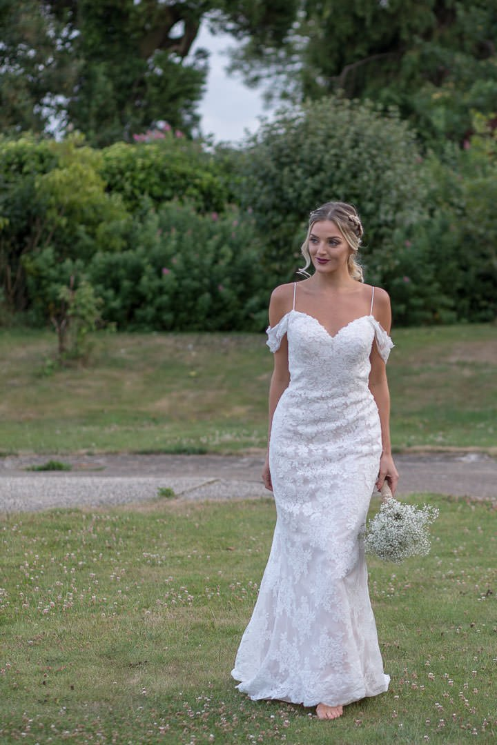 barefoot bride walks across grass holding bouquet for this Hampshire photography shoot