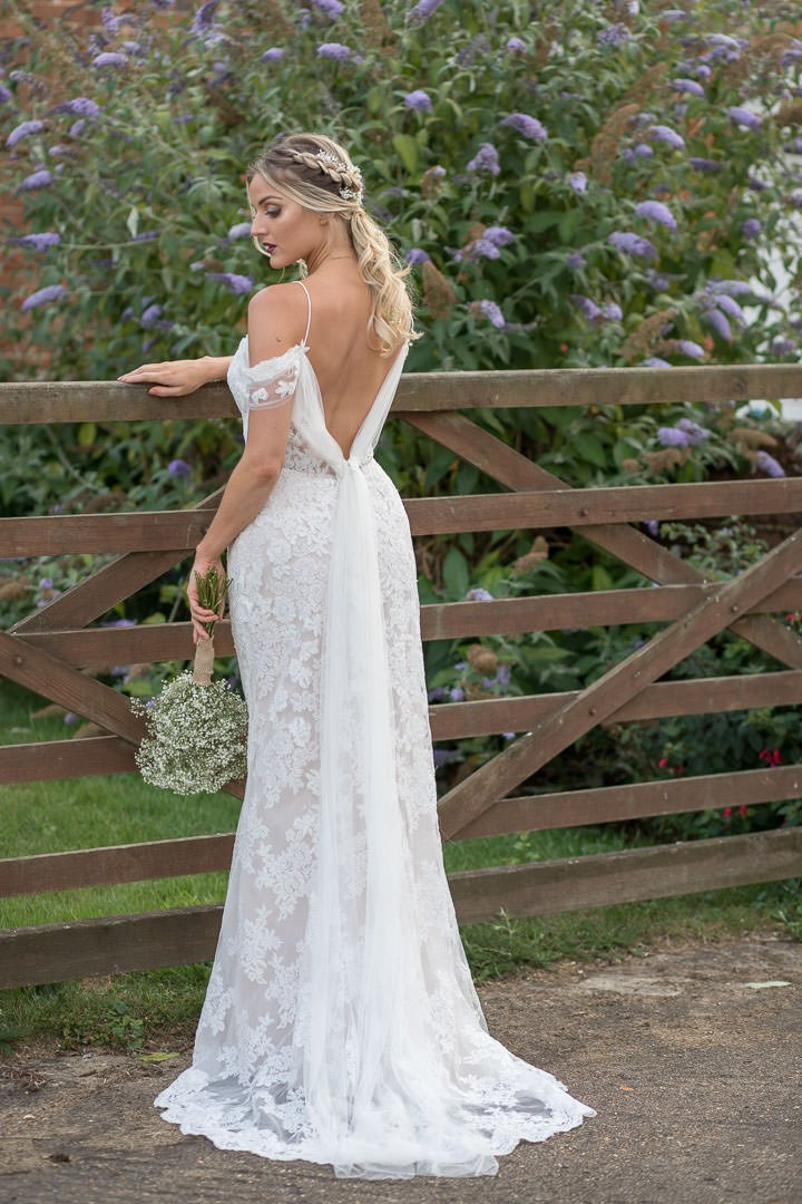full length back view of bride in white lace dress standing by gate as she looks down at her bouquet of gypsophilia