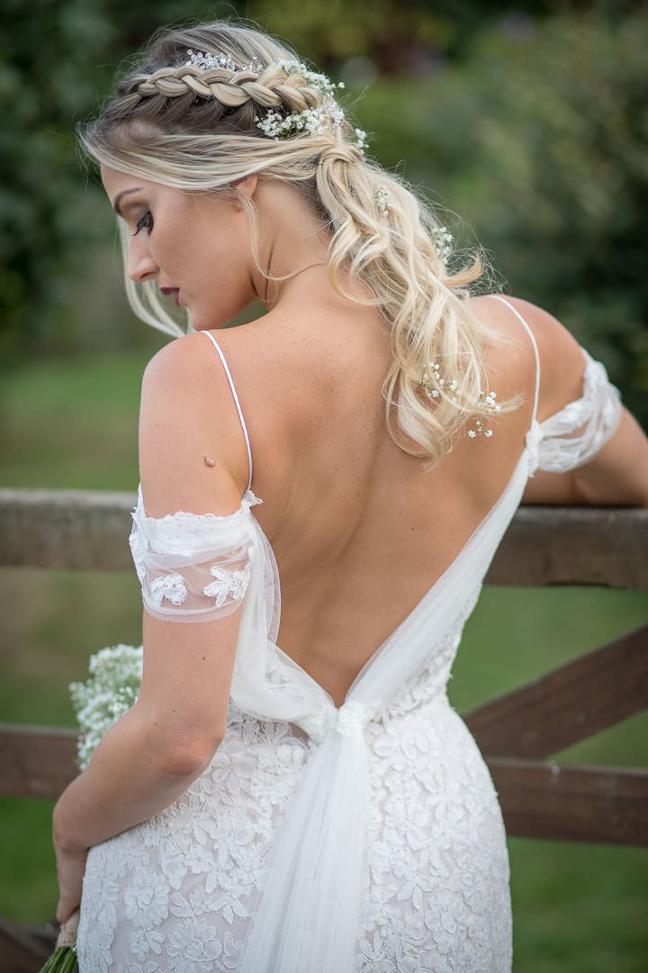 back view of bride in white lace dress standing by gate as she looks down at her bouquet of gypsophilia