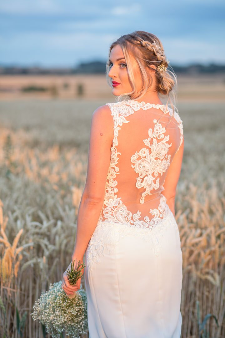 Boho Bride in white lace dress, holding bouquet of gypsophilia standing in a Hampshire cornfield during golden hour