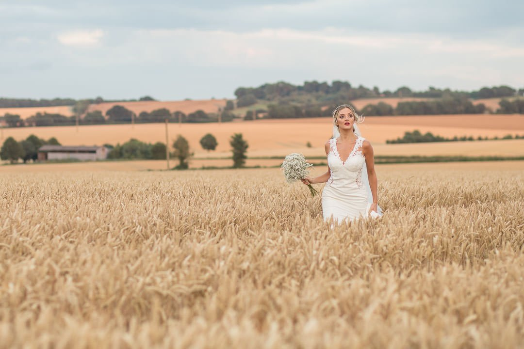 Boho Bride in white lace dress with veil, holding bouquet of gypsophilia walking in a Hampshire cornfield