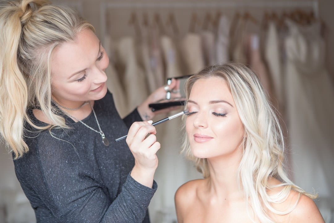 smiling blonde bride has her eye shadow applied for bridal photography shoot