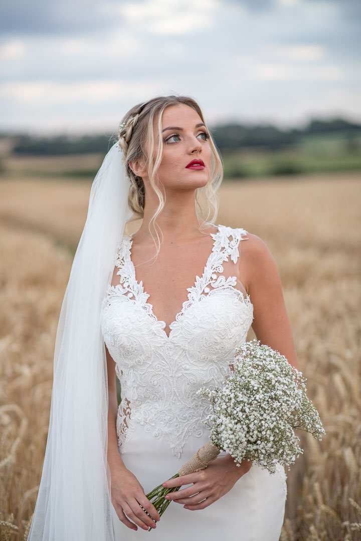 Bride in white lace dress with veil, holding bouquet of gypsophilia and standing a Hampshire cornfield