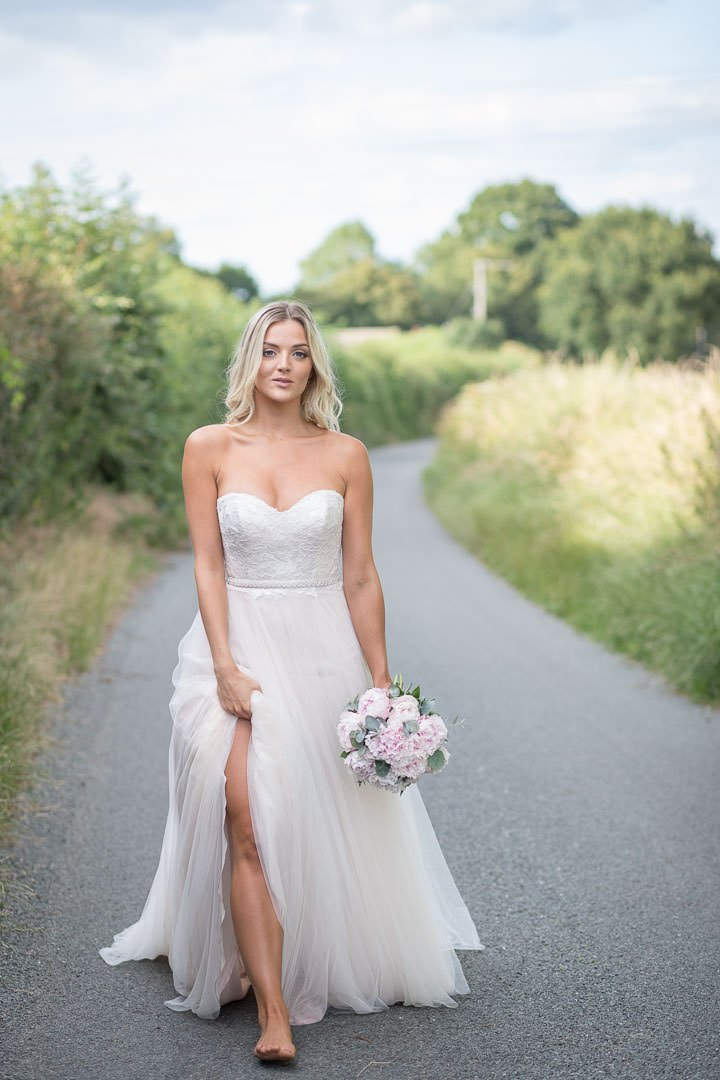 Barefoot bride walks down the Hampshire country lane showing legs