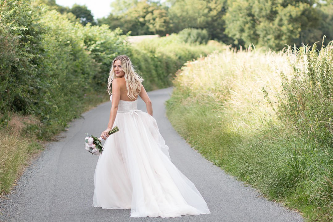 Boho bride dances down the Hampshire country lane as she holds up her dress and her bouquet of peonies