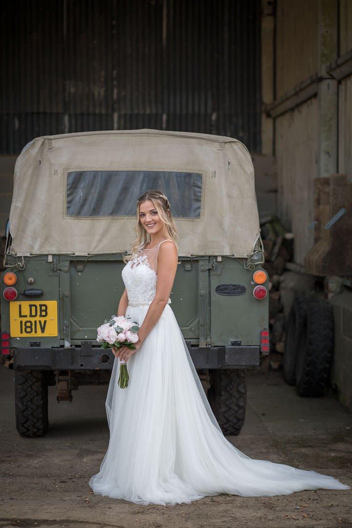 Bride smiles in the Hampshire farmyard as she poses near a Landrover Defender