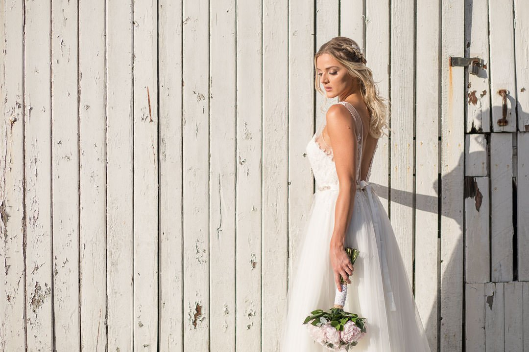 Bride stands by white farm doors in strong sunlight