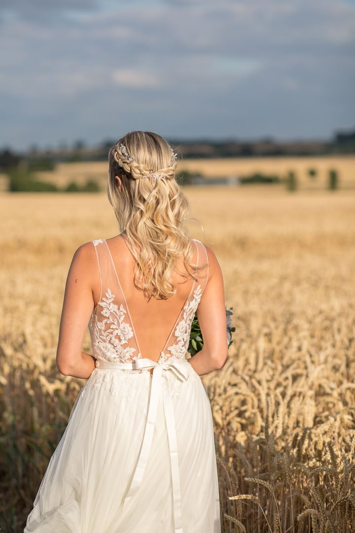 back view of ribbon tied lace dress as bride gazes into distance of the Hampshire cornfields