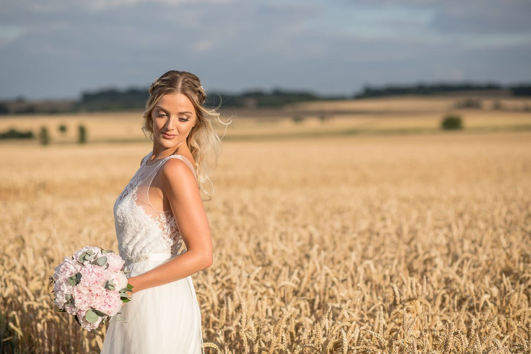sun-kissed bride with peony bouquet poses in a Hampshire cornfield