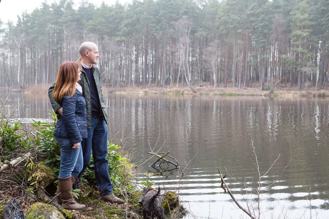 engagement photography session in Swinley forest, couple look at Rapley lake in swinley forest