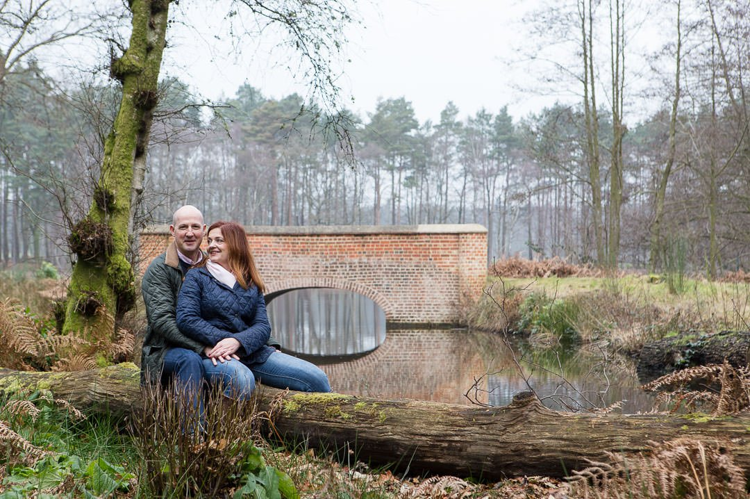 engagement photography session in Swinley forest, couple pose for a photograph by Rapley Lake in Swinley forest