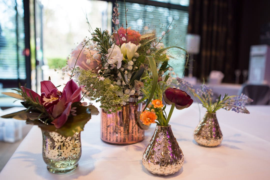 wedding flower arrangement of different vases of flowers at The Village hotel in Farnborough wedding fair