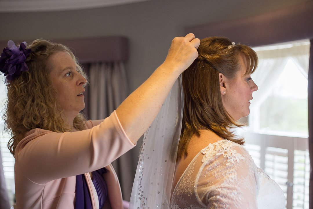The bride has her veil arranged by her sister at Oakley hall before the ceremony