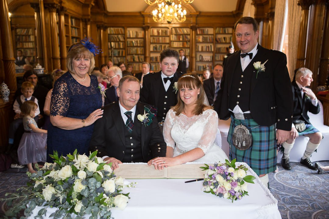 bride and groom signing the register at Oakley hall in Hampshire