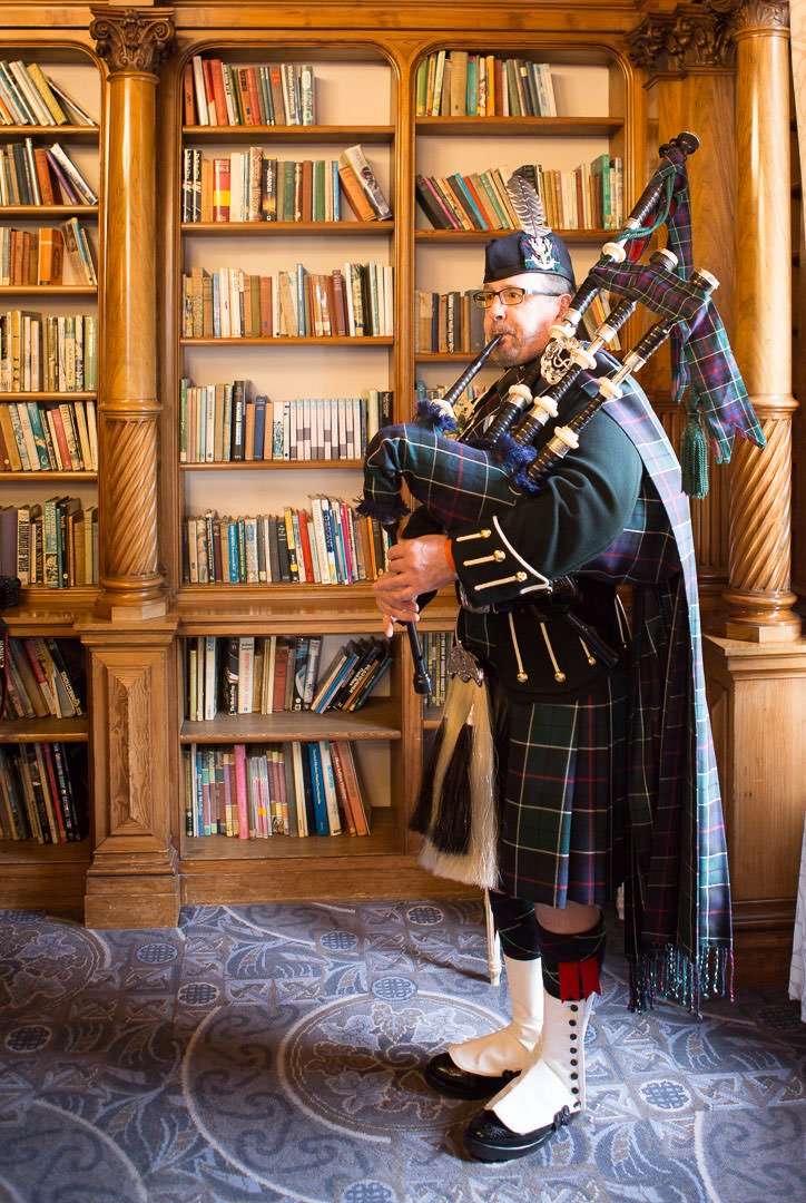 Scottish bagpiper at Oakley Hall in the library