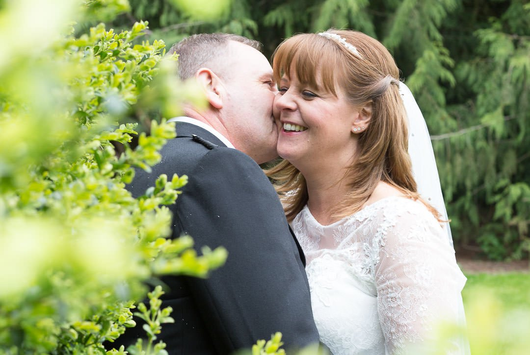 kissing and laughing bride and groom at Oakley Hall in Hampshire