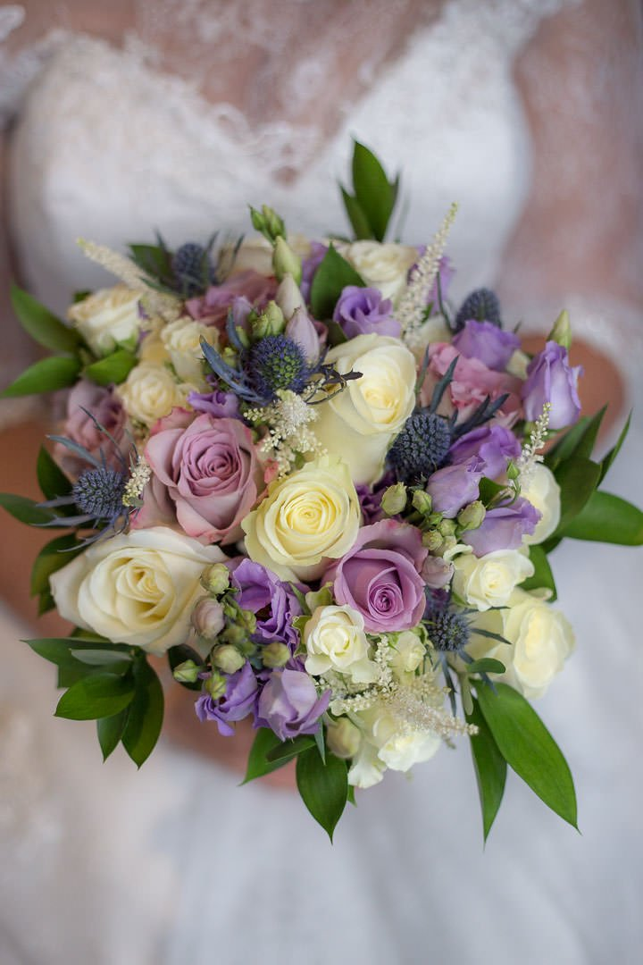 bride's bouquet consists of cream and mauve roses, purple lisianthus and blue eryngium