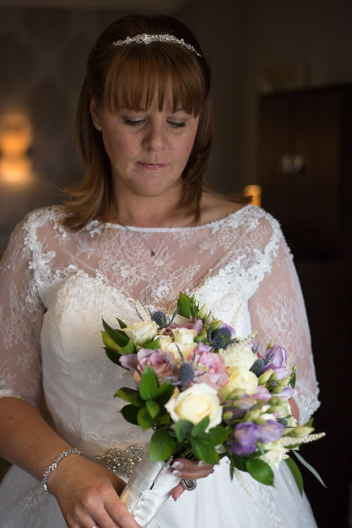 The bride looks at her bouquet before the ceremony at Oakley Hall in Hampshire