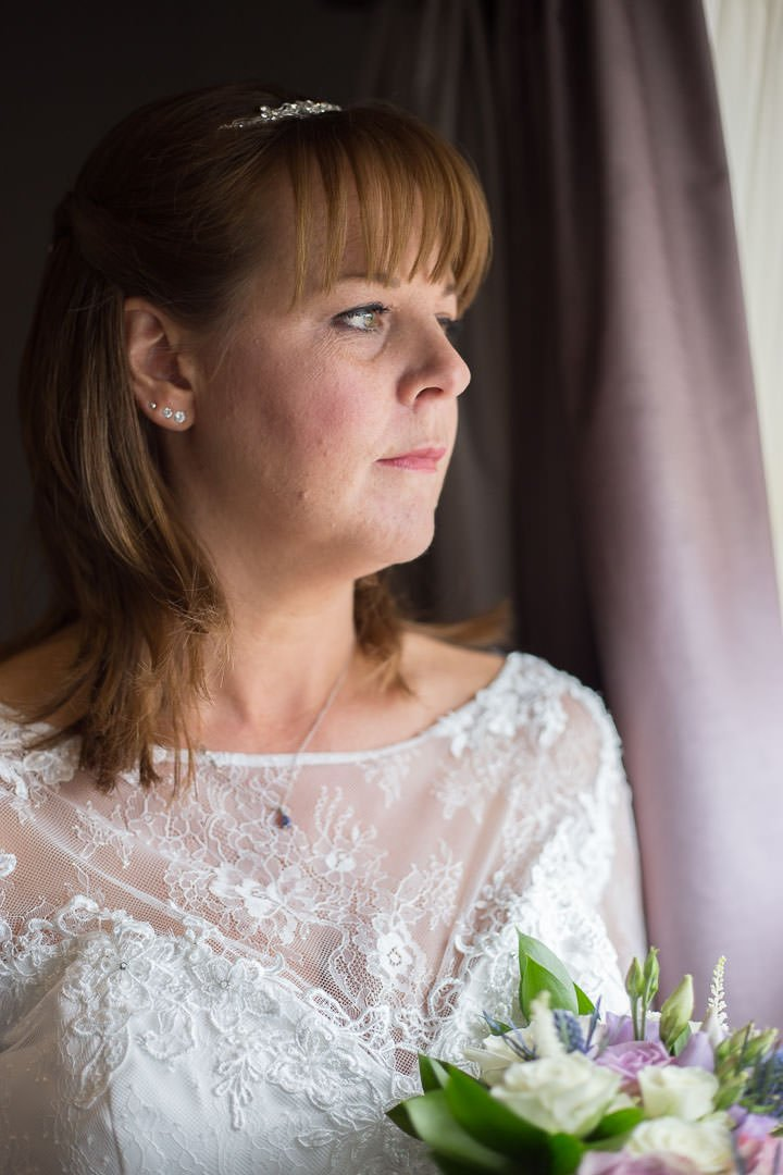 The bride looks out of the window at Oakley Hall in Hampshire